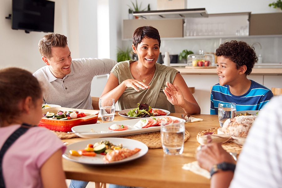 About Our Agency - Family Talking and Eating Meal Around Table At Home Together