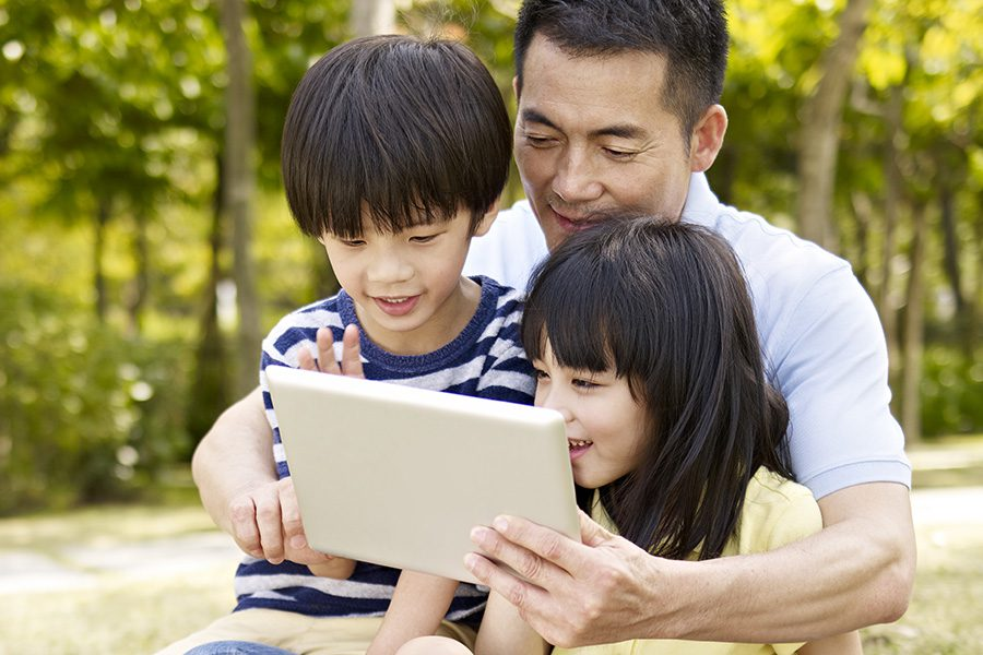 Client Center - Father and Two Children Using Their Tablet Outdoors in Front of Trees