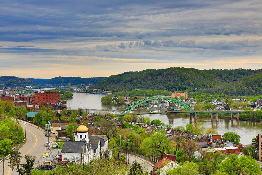 Columbiana, OH - Aerial View of Wheeling, West Virginia Along the Ohio River Displaying buildings and Mountain Range in the Background