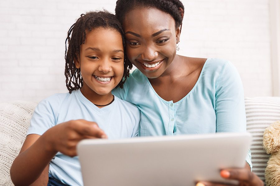 Contact - Mom and Daughter Making a Video Call on a Tablet at Home