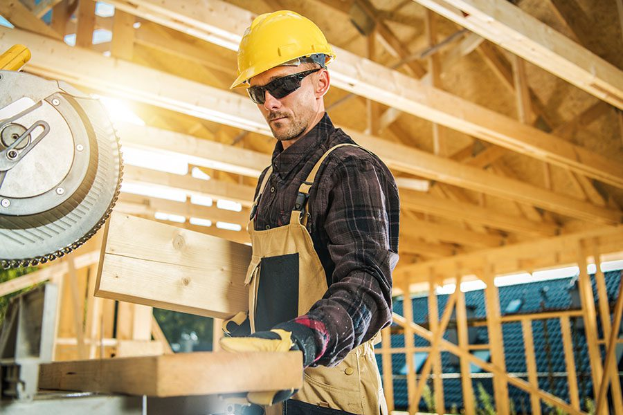 Specialized Business Insurance - Carpenter Preparing Some Wood to Cut to Use in a House Structure Project