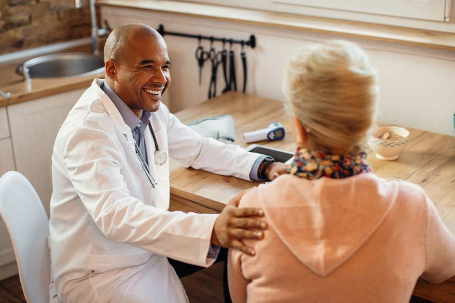 Medicare Advantage Plans - Smiling Doctor Talking to a Woman Patient While Visiting Her at Home