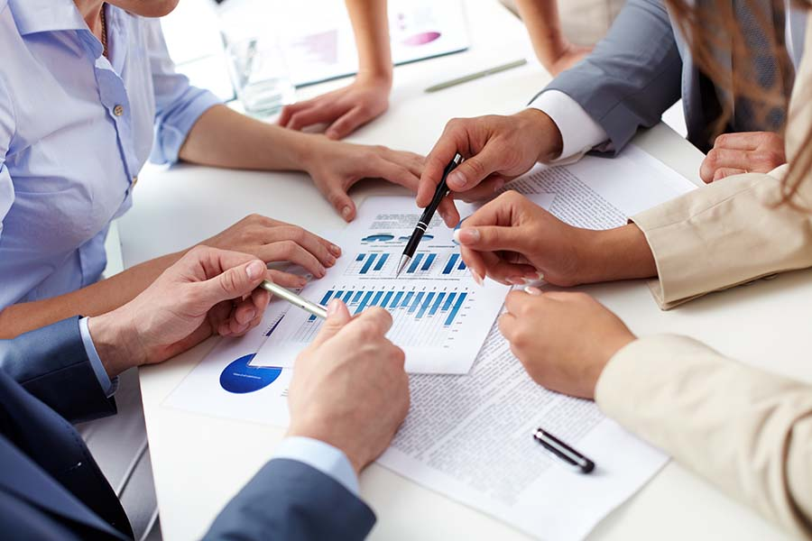 Workers Comp Analysis Program - Group of Consulting Professionals Gathered around a Conference Table and Examining Documents and Data