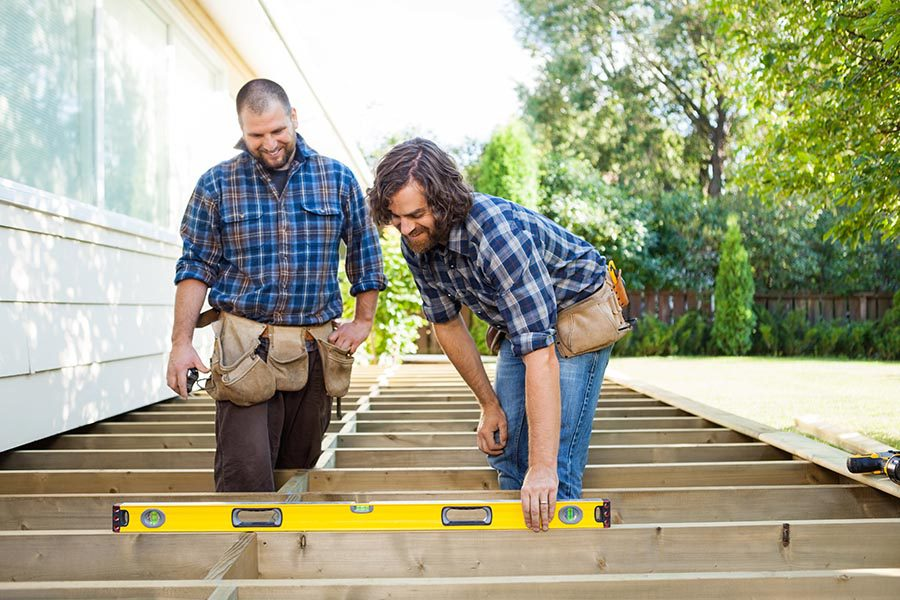 Business Insurance - Two Contractors Work Together to Build a Deck Onto a Home