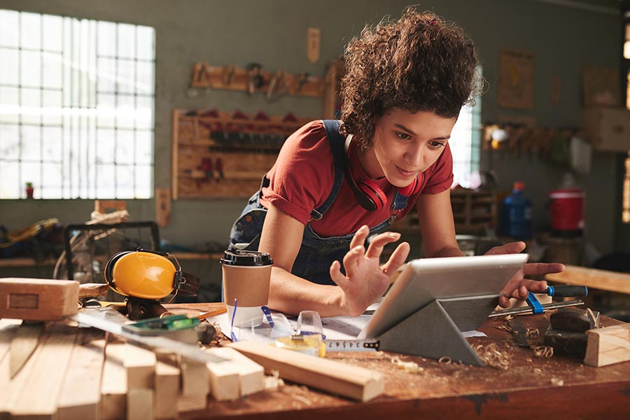 Client Center - Young Craftsman Uses a Tablet at Her Work Bench in a Wood Studio