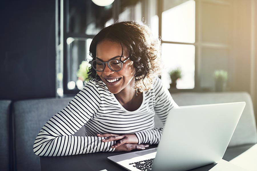Insurance Quote - Young Woman Uses a Computer in a Cafe, Smiling and Wearing Glasses