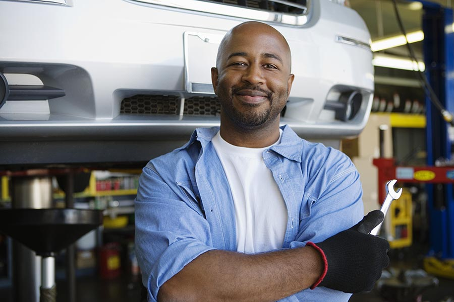 Specialized Business Insurance - Proud Auto Repair Shop Owner Wearing a Blue Shirt and Holding a Wrench