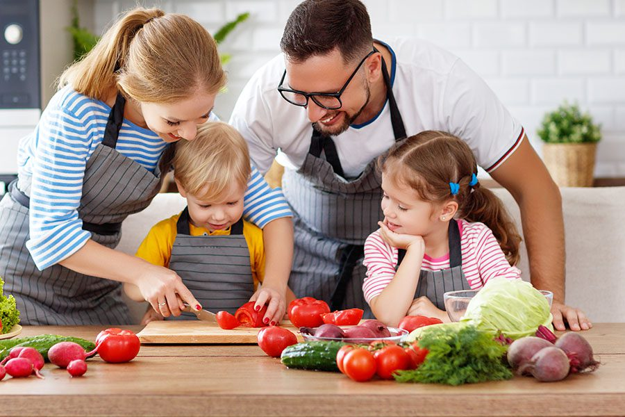 Personal Insurance - Happy Family With Children Preparing Vegetable Salad