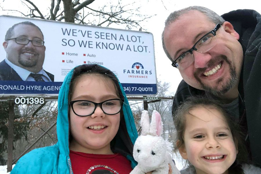 About Our Agency - Ronald Hyre and Family Standing in Front of Self Promotion Billboard