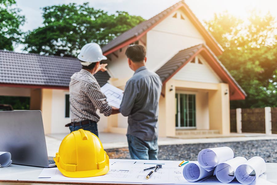 Course of Construction Insurance - Two Professional Engineers Discussing Progress of Construction on a New House