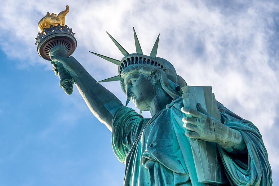 Immigration Bonds - Statue of Liberty against Blue Sky in New York City