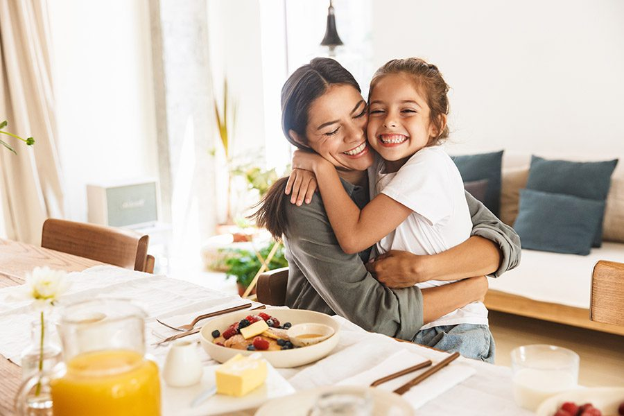 Personal Insurance - Happy Mother and Daughter Hugging While Having Breakfast at Home in Morning