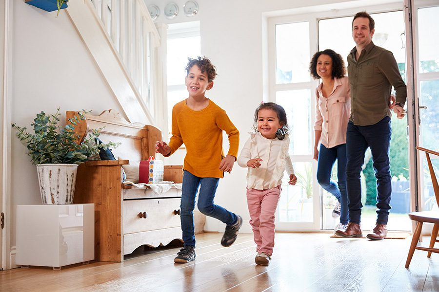 Blog - Excited Family Returning Home After a Long Trip With Children Running on Ahead