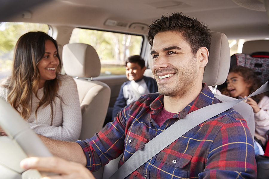 Personal Insurance - Mother Turning Around to Speak to Her Children in the Back Seat of Car During a Family Outing