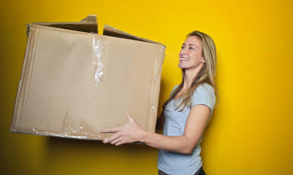 Your Renters Insurance Survival Guide - Woman Carrying Very Large Box Against a Yellow Wall