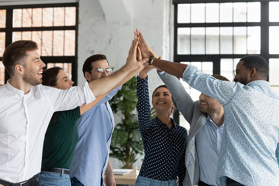 About Our Agency - Cheerful Group of Coworkers Putting Their Hands Together to Celebrate Success in the Office