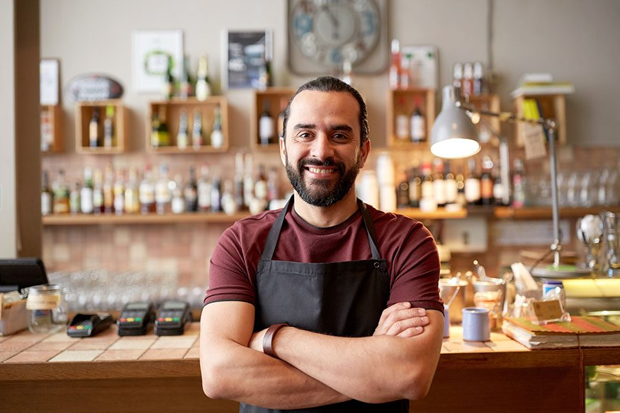 Business Insurance - Portrait of a Cheerful Young Small Business Man Standing in His Shop with His Arms Folded