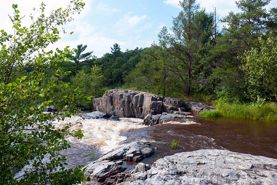 Eau Claire WI - Scenic View of a Waterfall Surrounded by Green Trees in Eau Claire Wisconsin on a Sunny Day