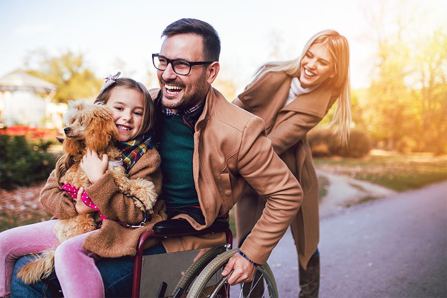 Employee Benefits - Portrait of a Cheerful Mother Pushing Her Husband in a Wheelchair with Their Daughter and Dog Sitting on His Lap in the Park
