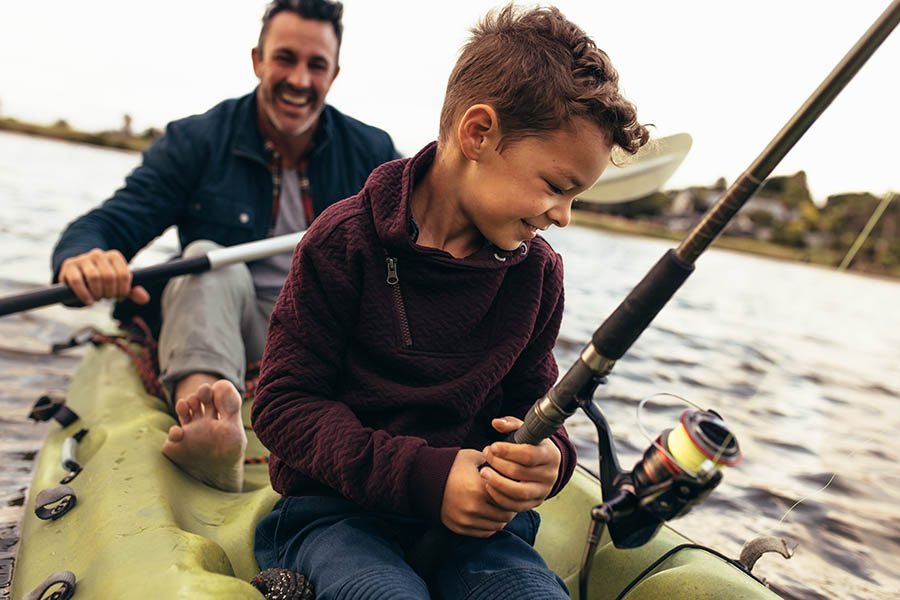 Employee Benefits - Father and Son Enjoying Fishing in the Lake at Sunset