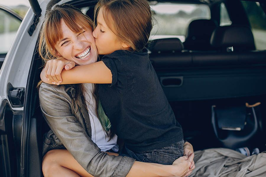 Personal Insurance - Mother and Daughter Sitting in the Trunk of Car Before a Road Trip