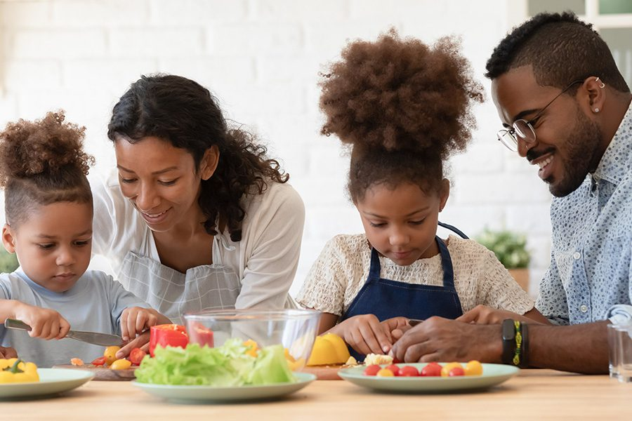Employee Benefits - Loving Young Parents Preparing Healthy Food Salad With Little Kids in Kitchen