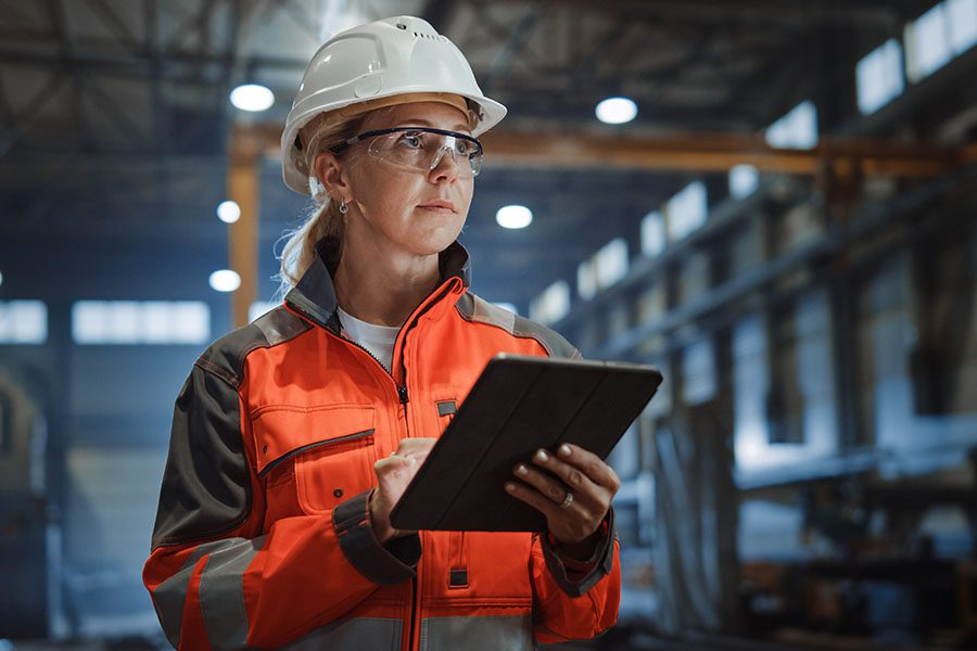Specizlized Business Insurance - Closeup Portrait of a Young Woman Standing in a Manufacturing Facility While Holding a Tablet in Her Hands