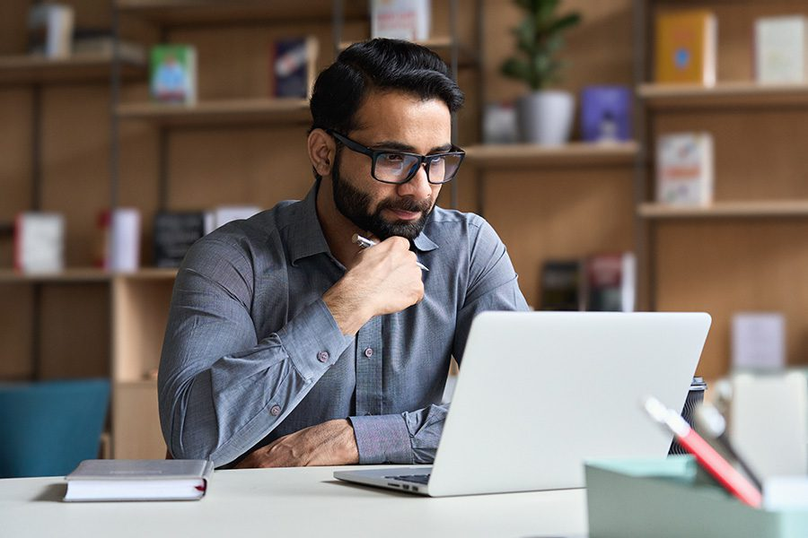 Claim Assistance - Portrait of a Young Businessman Sitting at His Desk in the Office While Using a Laptop