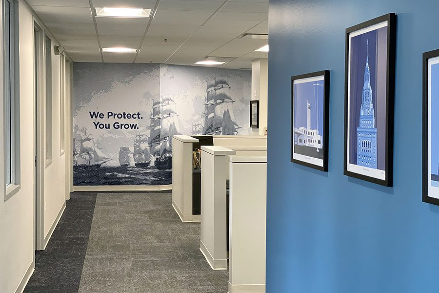 About Our Brokerage - View of a Hallway in the Armada Risk Partners Office Building with We Protect You Grow Tagline on Wall