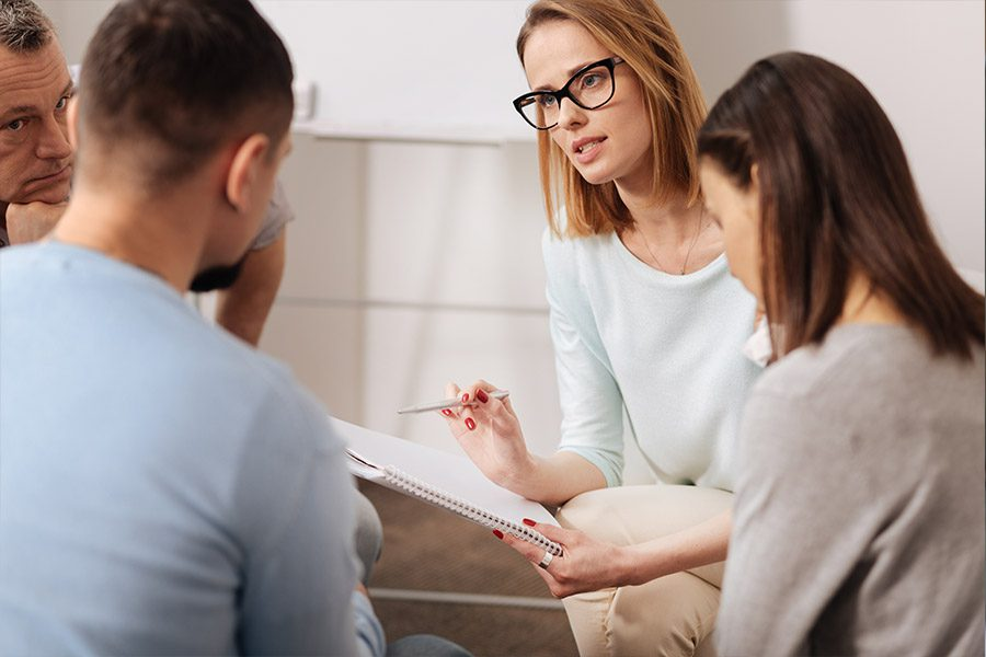 Social Service Agency Insurance - Woman Talking with a Family About Social Work Options