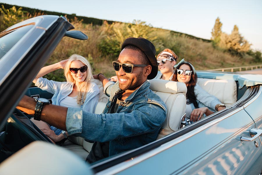 Blog - Friends Riding in a Convertible on a Sunny Day, All Smiling and Wearing Sunglasses