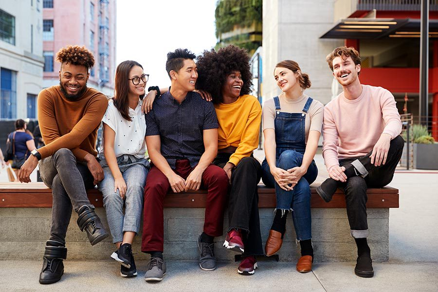 Employee Benefits - Diverse Group of Young Men and Women Sit on a Bench Wearing Colorful Clothing, All Smiling and Chatting