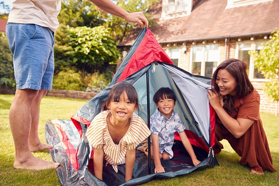 Personal Insurance - Young Family Playing in a Tent in Their Yard, Kids Climbing Out and Laughing