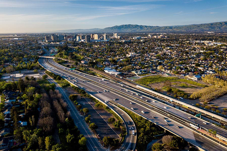 San Jose, CA Insurance - Aerial View of San Jose, California and Silicon Valley, Busy Highways and High Rise Buildings, Hills in the Distance