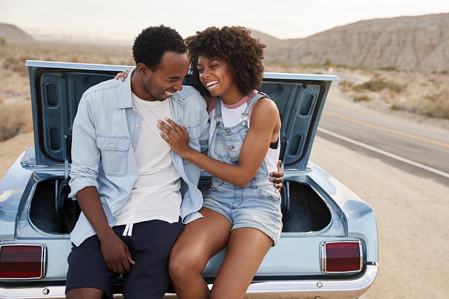 About Our Agency - Young Couple Laughs As They Sit In the Back of Their Classic Car on a Desert Highway at Sunset