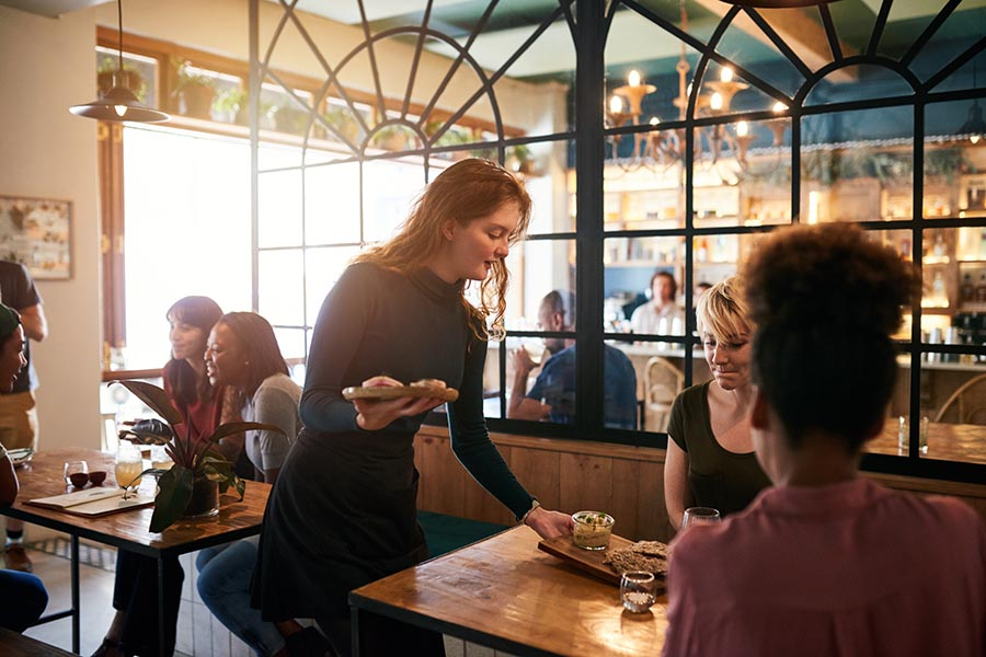 Specialized Business Insurance - Waitress Serves a Table of Young People at a Charming Restaurant, Sun Streaming Through the Windows