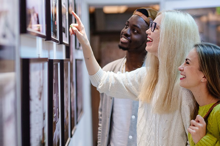 Art Gallery Insurance - Three Young Students Looking at a Picture on the Wall in an Art Photo Gallery
