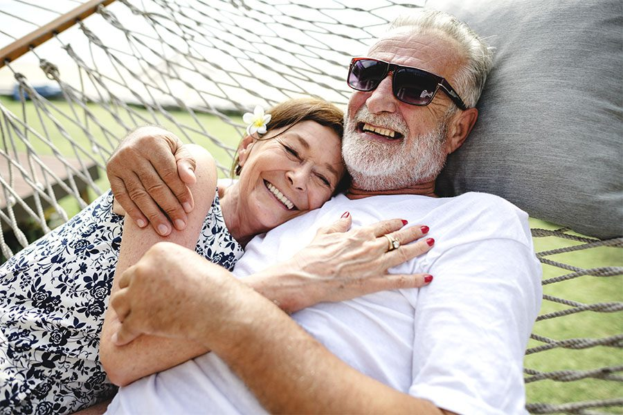 Employee Benefits - Closeup Portrait of a Cheerful Elderly Couple Relaxing in a Hammock in the Backyard on a Warm Summer Day