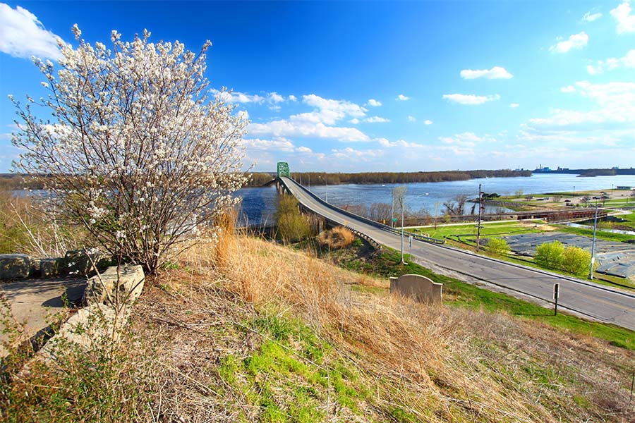 Muscatine IA - View of an Empty Bridge Across the River Surrounded by Grass and Blooming Foliage in Muscatine Iowa