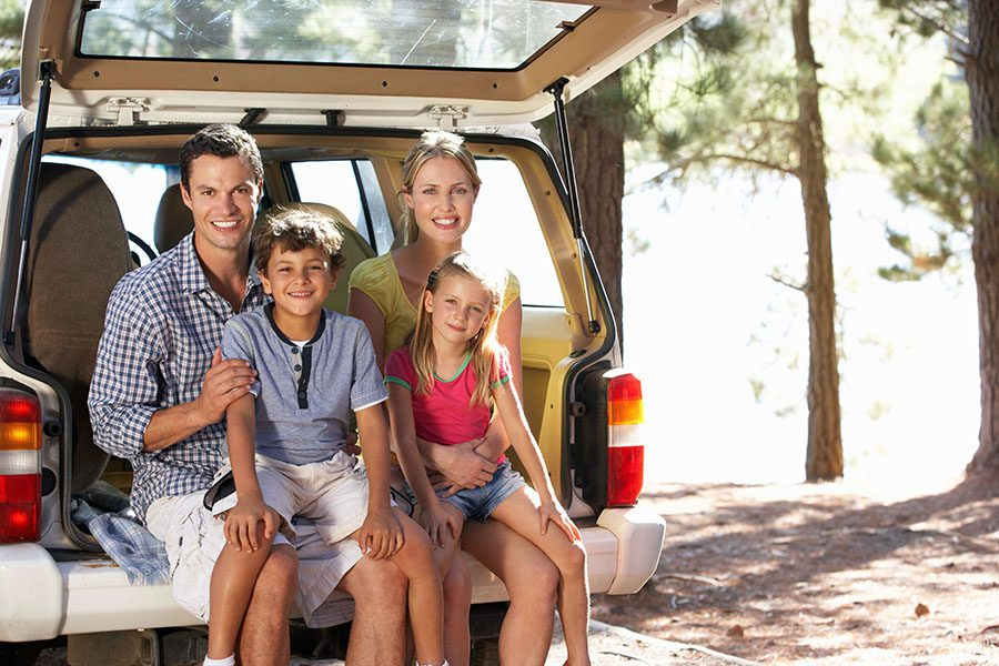 Personal Insurance - Closeup Portrait of a Cheerful Family with Two Kids Sitting in the Back Trunk of Their Car While on a Summer Vacation to the Lake