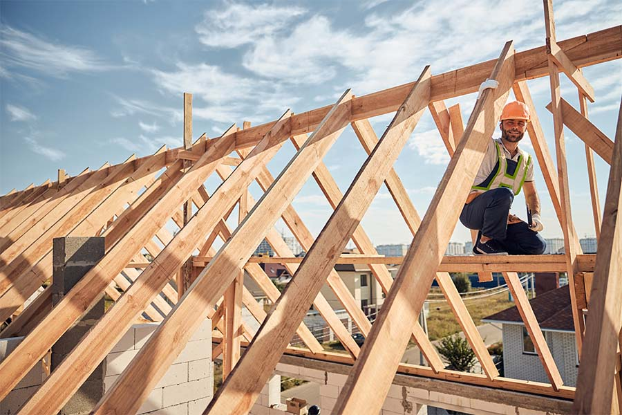 Specialized Business Insurance - Portrait of a Smiling Contractor Working on Building the Frame of a Roof for a New Home