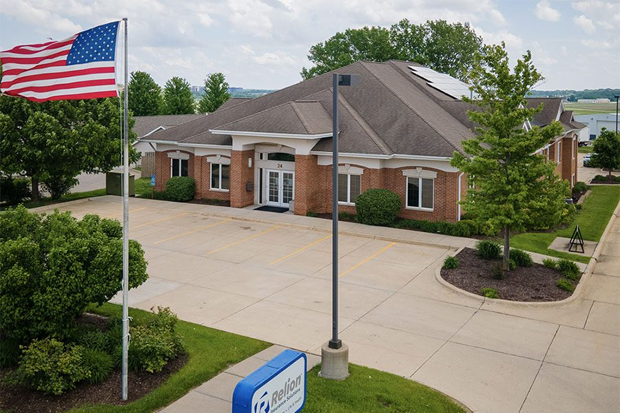 About Our Agency - View of Relion Insurance Solutions Office Building with an Empty Parking Lot and Green Landscaping