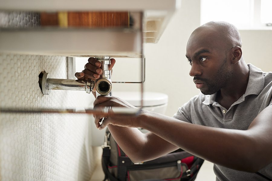 Plumbing Contractor Insurance - Closeup of a Male Plumber Sitting on the Floor and Fixing a Bathroom Sink