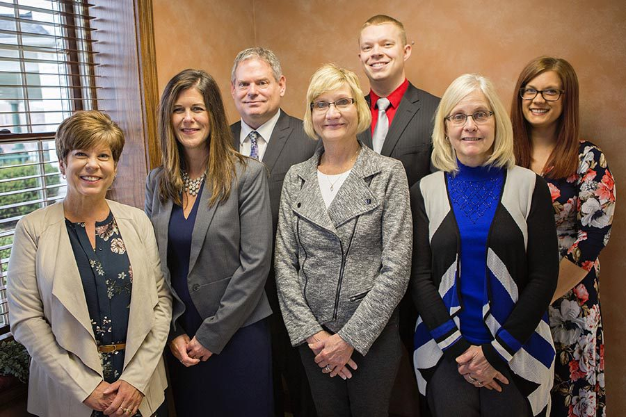 About Our Agency - Group Photo of Everett Schmenk Insurance Agency, Featuring Seven Team Members Nicely Dressed and Standing Together in Their Office