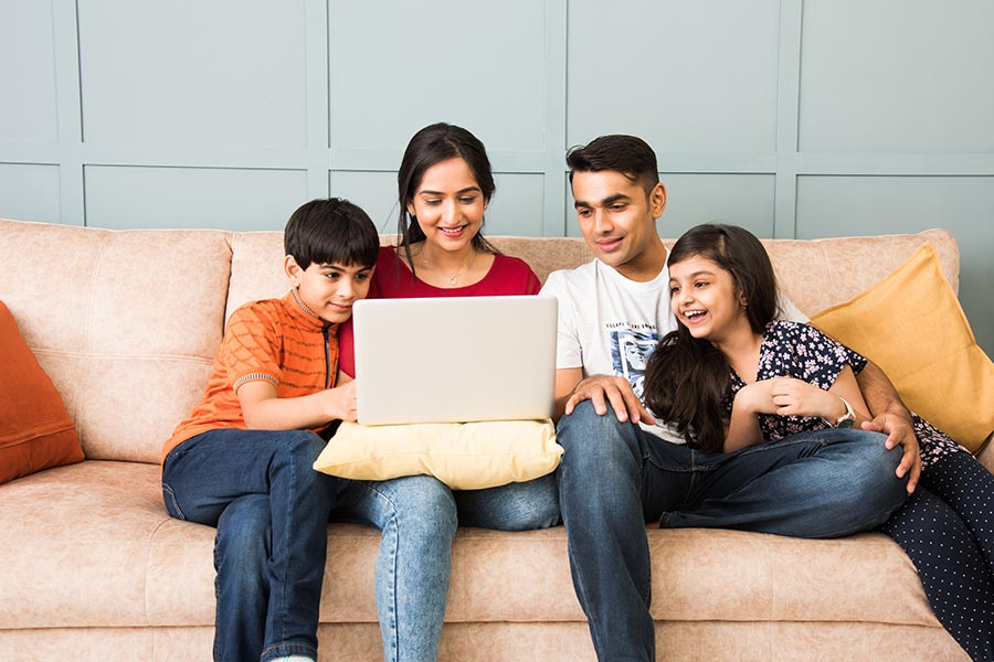 Client Center - Family Sitting Close on a Couch Using a Laptop, Parents With Their Arms Around the Pre-Teen Children