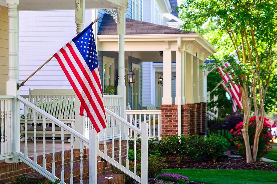Kalida, OH Insurance - American Flags on Front Porches, Green Grass and Flower Beds Between Them