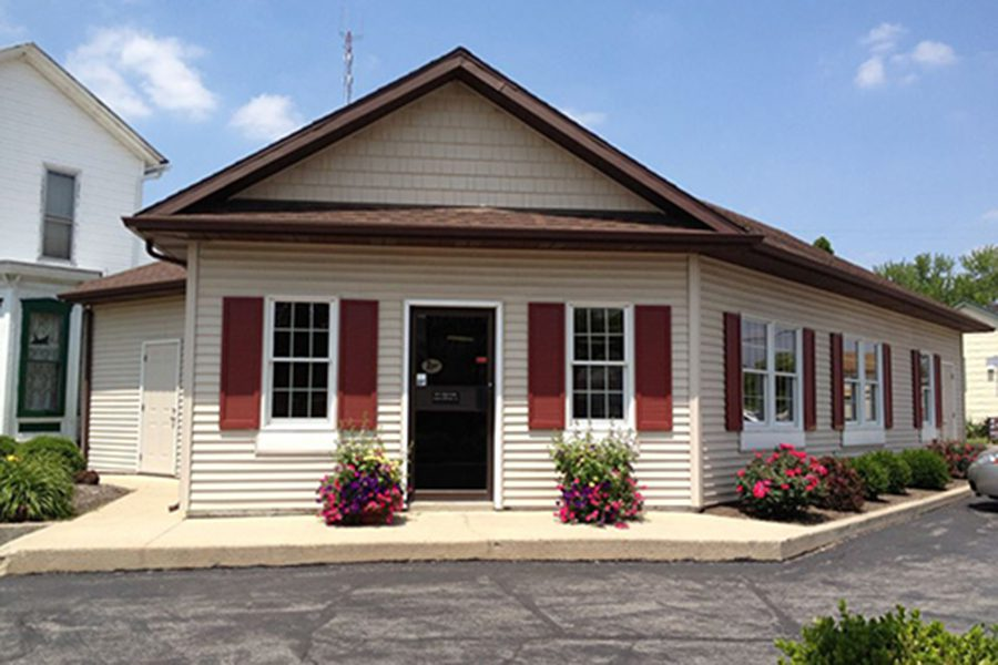 Ottawa, OH Insurance - Office Location of Everett Schmenk Insurance Agency in Ottawa, Ohio, A Charming Building With Cream Colored Siding, Red Shutters, and Flowerpots