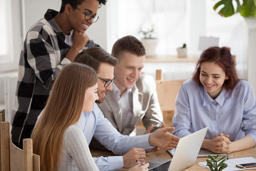 Blog - Young Employees at an Office Table Brainstorming Together, Smiling, and Casually Discussing Project