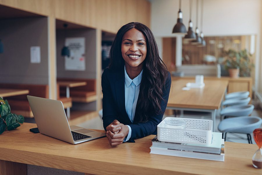Business Insurance - Businesswoman Working At Her Desk in a Large Modern Office