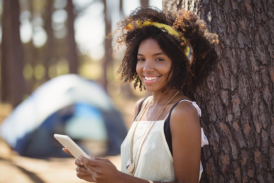 Campground Insurance - Portrait of Young Girl Using Smart Phone in Forest with Tent Blurred in the Background